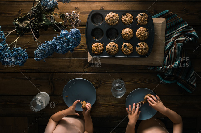 Overhead view of two little boys eating fresh homemade muffins