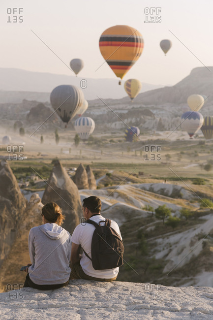 Rear view of young couple looking at flying balloons, Cappadocia, Turkey