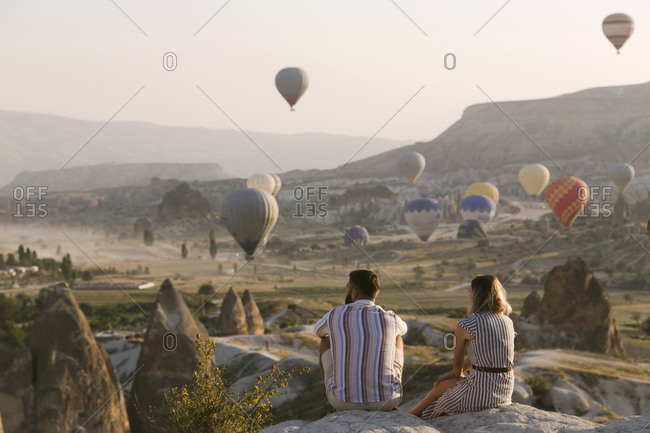 Young couple looking at hot air balloons, Cappadocia, Turkey
