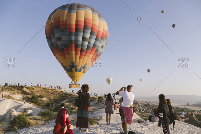 Cappadocia, Turkey - Jul 31, 2019: People watching hot air balloons at Cappadocia