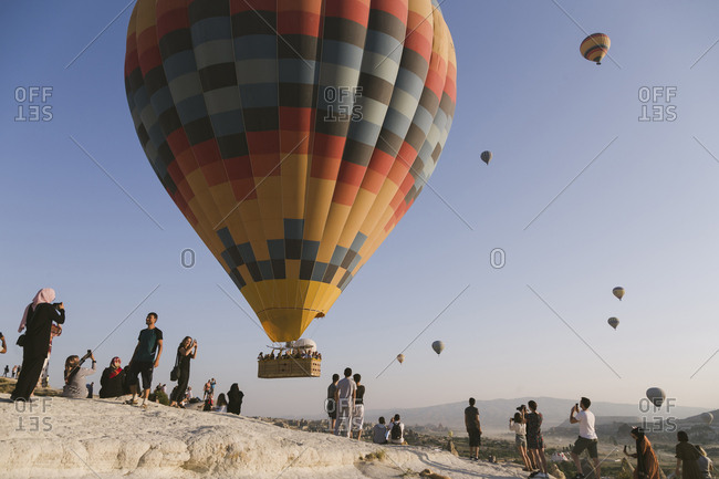Cappadocia, Turkey - Jul 31, 2019: People watching hot air balloons at a balloon festival