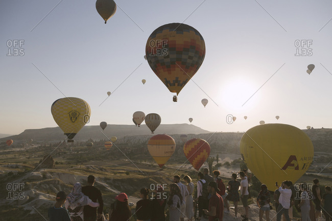 Cappadocia, Turkey - Jul 31, 2019: People watching hot air balloons at sunset