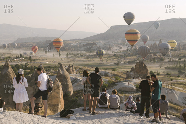 Cappadocia, Turkey - Jul 31, 2019: Group of people watching hot air balloons at sunset