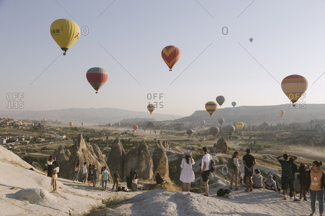 Cappadocia, Turkey - Jul 31, 2019: Group of people watching colorful hot air balloons at sunset