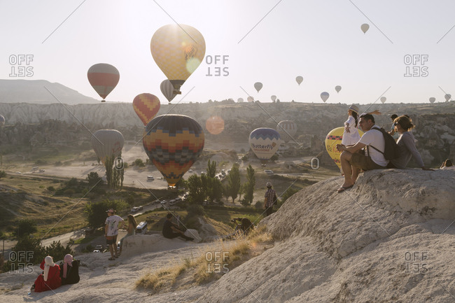 Cappadocia, Turkey - Jul 31, 2019: People on mountain watching colorful hot air balloons at sunset