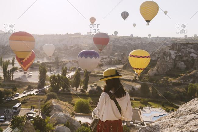 Woman looking at flying balloons, Cappadocia, Turkey