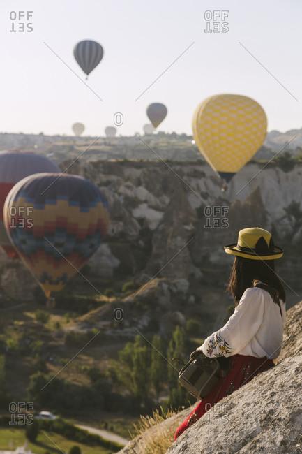 Woman wearing hat looking at flying balloons, Cappadocia, Turkey