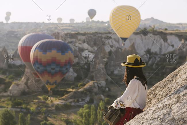 Woman watching at flying balloons, Cappadocia, Turkey