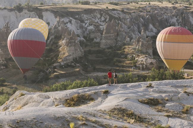 Young couple hiking and looking at flying balloons, Cappadocia, Turkey