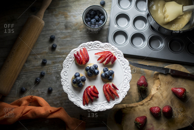 Preparing berry tartlets with cream and fresh fruits