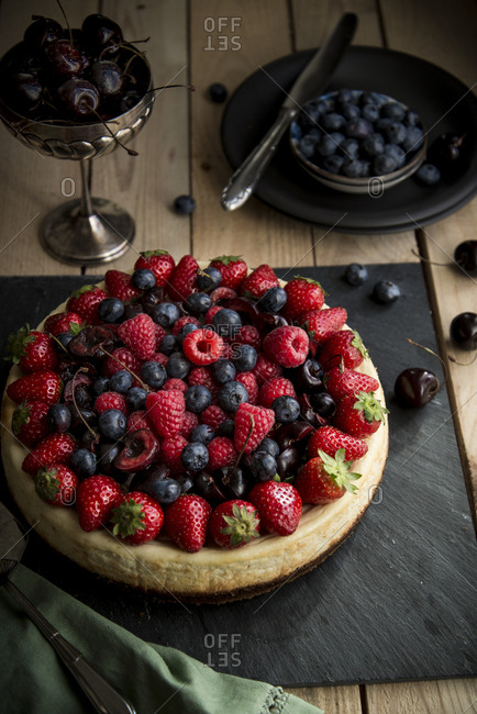 Ricotta cake on a square slate board topped with a variety of fruit