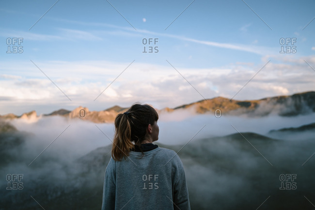 Blonde girl with ponytail watching the sunset in the mountains
