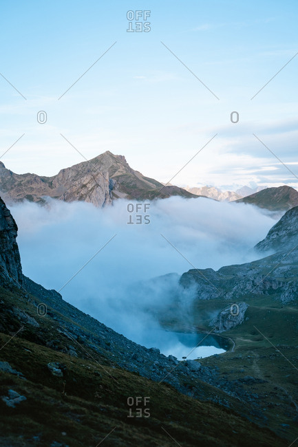 Clouds covering a high altitude lake in the mountains during sunset