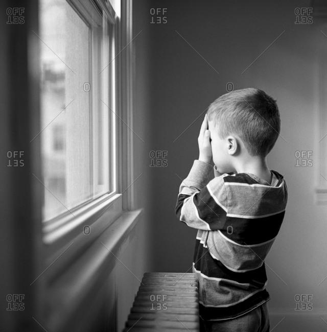 Boy facing window covers his eyes