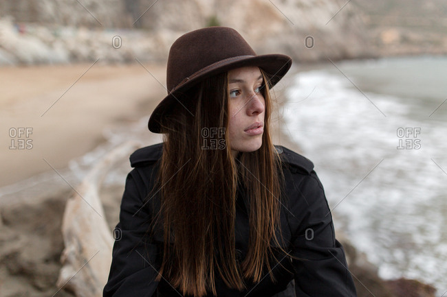 Portrait of young woman with hat and trench coat on the beach in a cloudy day of winter