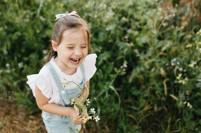 Girl laughs as she picks flowers