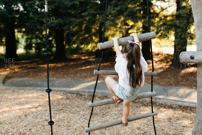 Girl on playground climbs a wooden ladder
