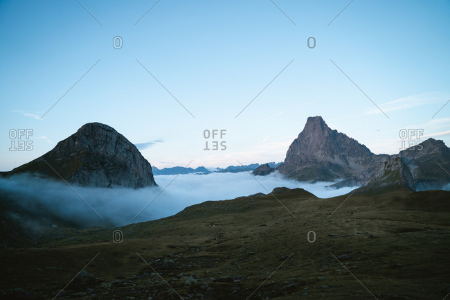 Two big mountains above the clouds during twilight