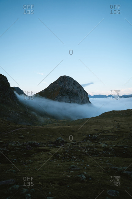 Big mountain above the clouds during twilight