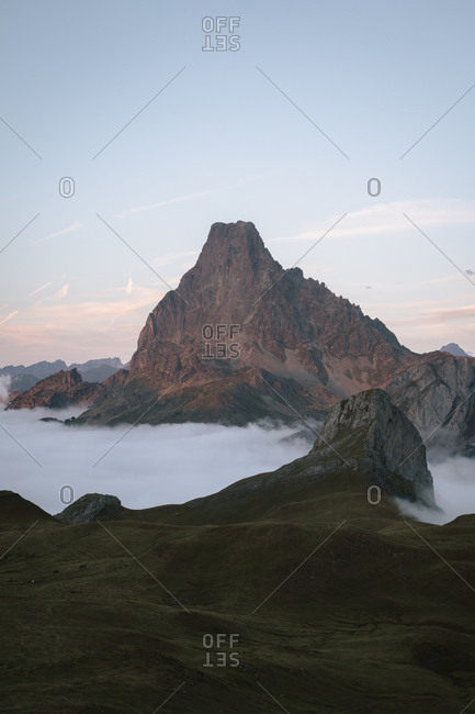 Sunset light in alpine landscape with low clouds at the bottom of big mountain