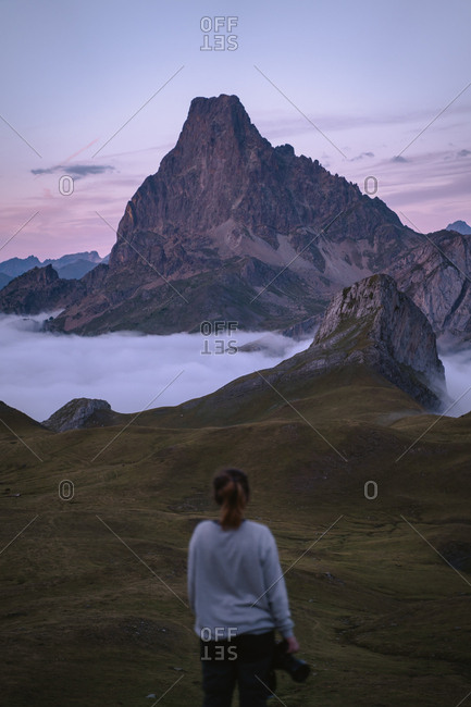 Lonely girl watching a beautiful alpine landscape during twilight