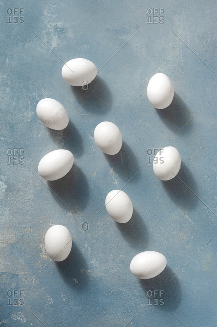 Overhead view white eggs on blue background