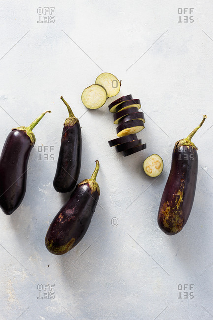 Overhead view of sliced and whole eggplants