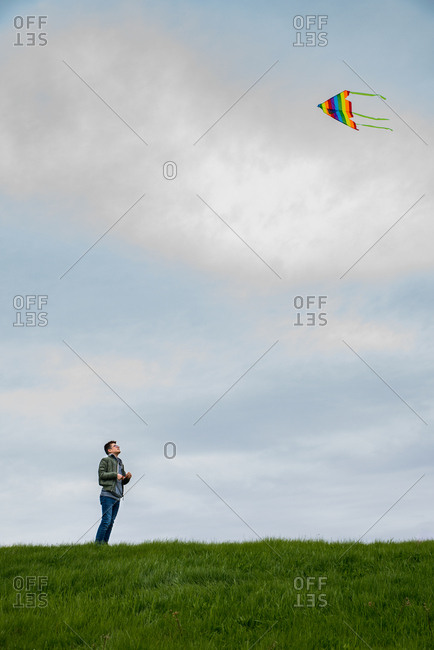 Teenage boy flying a colorful kite alone on a cloudy day.