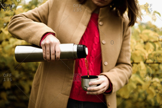Young woman  pouring tea from thermos flask into cup