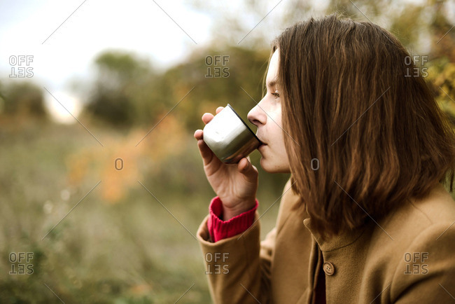 Young Woman Drinking Tea From A Thermos Outdoors.