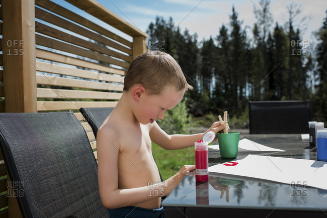 young boy painting outside in the sunshine
