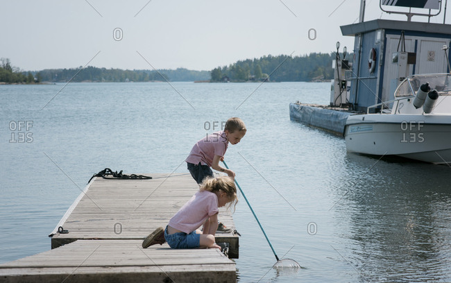 two kids fishing on a jetty in the sea