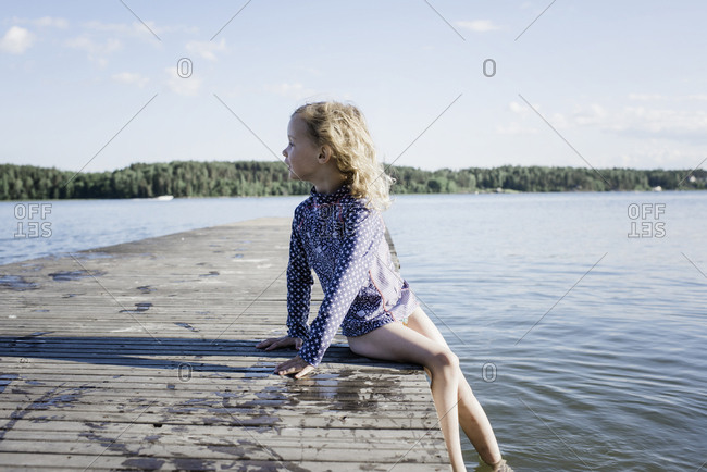 Young blonde girl sat on a pier looking out to see