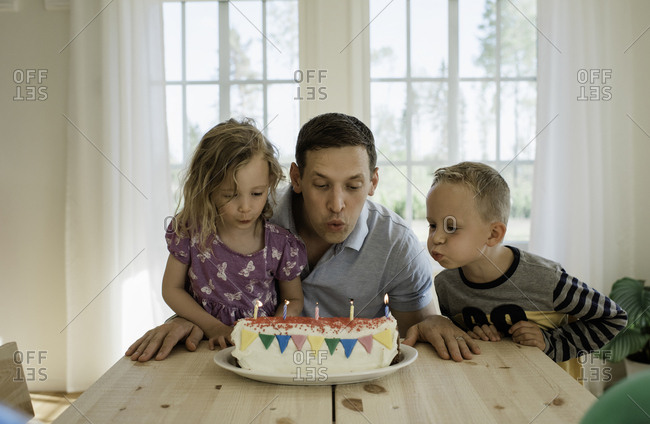 a father with his daughter & son blowing candles on a birthday cake