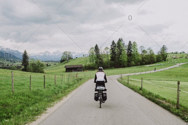 A cyclist riding in a beautiful landscape near to The Alps