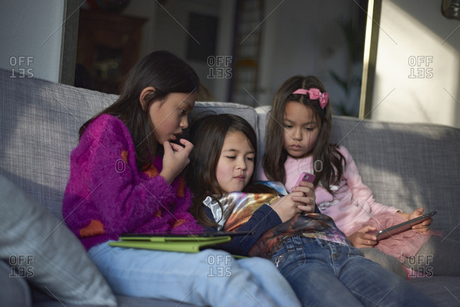 Three young Asian girls on the sofa playing with their tablet at home