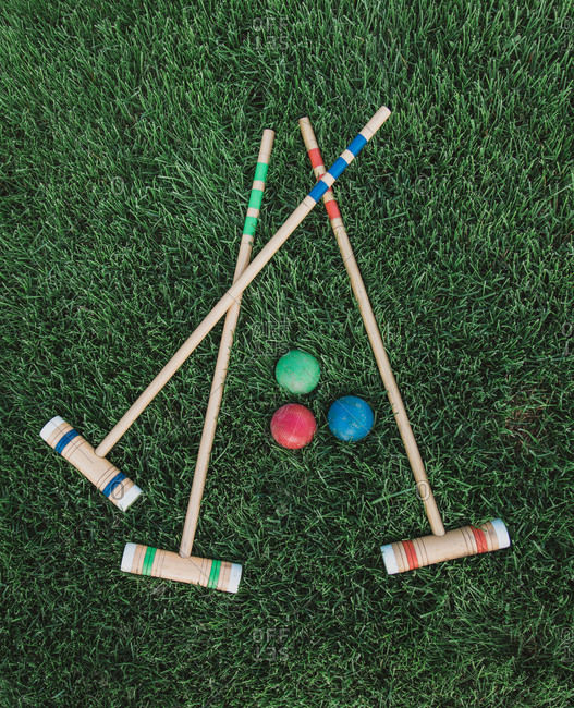 High angle shot of wooden croquet mallets and balls on the grass.