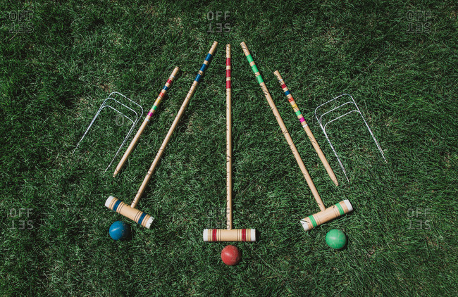 High angle shot of wooden croquet set on the grass.