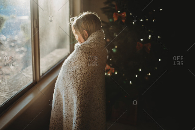 Girl with blanket staring out window