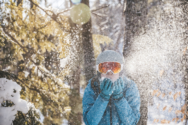 Woman in ski goggles and helmet in backlit snow scene in New Hampshire