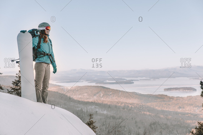 Woman with ski goggles and snowboard on mountain overlooking lake