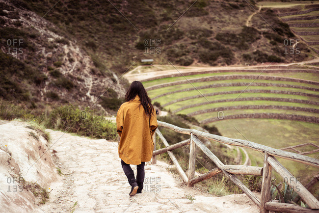 Person in jacket walks down steps of archaeological Inca ruins site