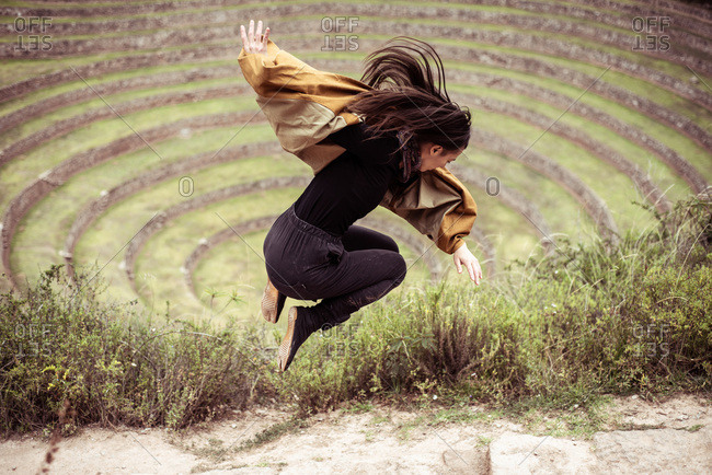 girl jumps in circle of archaeological Inca ruins sight
