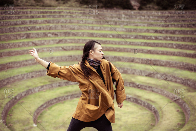 Dancer in jacket in center of ancient stone circles from Inca ruins