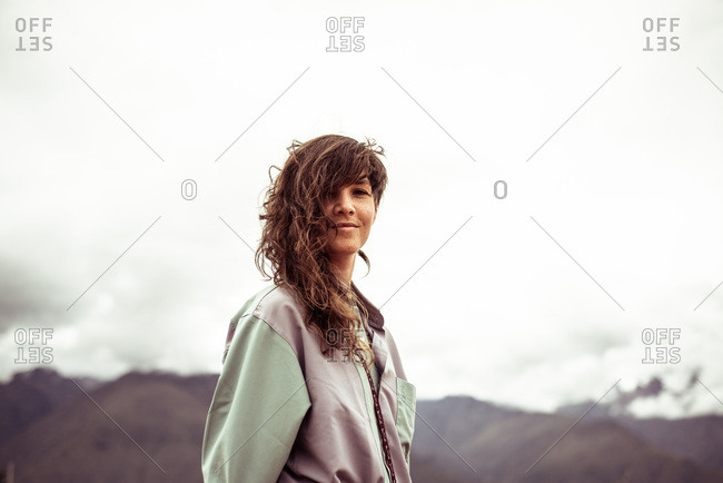 Girl with curly wild hair and shirt smiles at camera