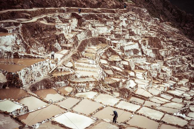 Men work in salt farms on mountain side in Maras