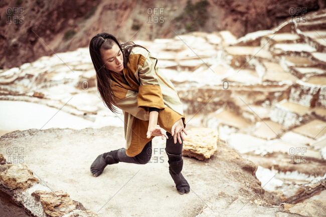 Androgynous mixed race dancer dances in salt farm on mountain side