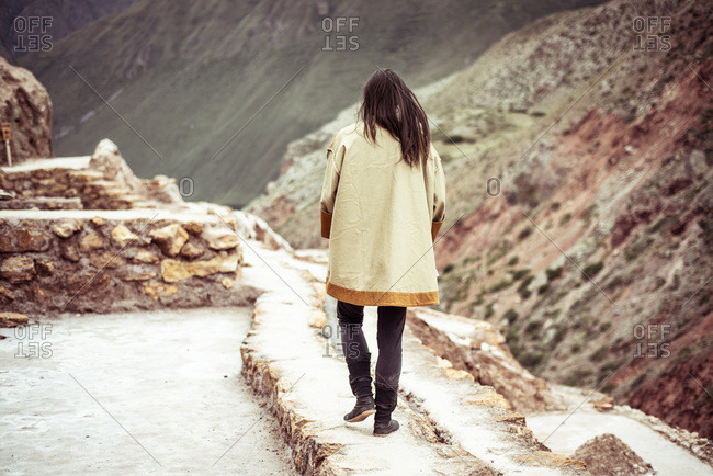 Androgynous dancer walks in salt farm on mountain side