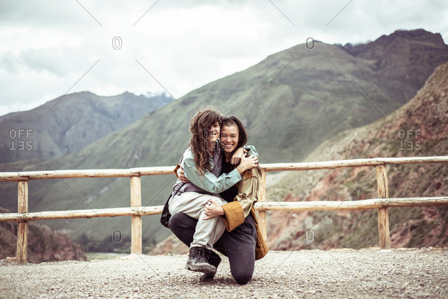 lesbian couple laugh and hold each other in travel selfie