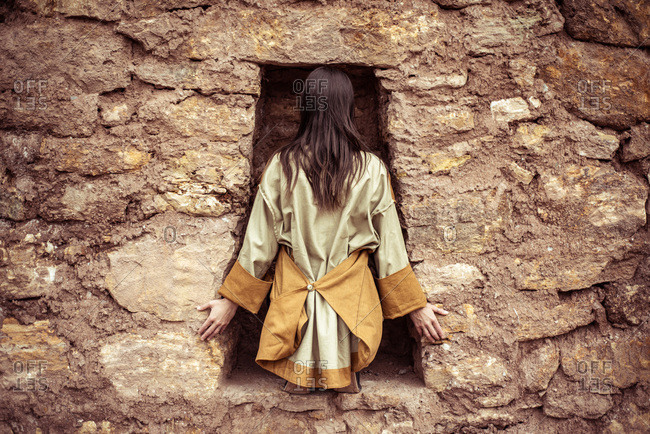 dancer with high fashion jackets sits in key hole in stone wall